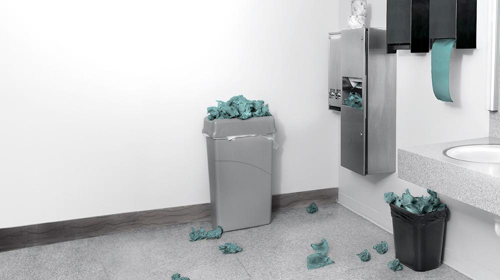 Toaletă cu prosoape de hârtie pe podea și coșuri pline