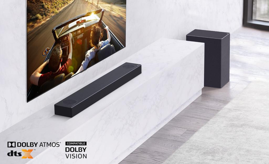 Televizorul este amplasat pe perete, soundbarul LG este instalat dedesubt, pe un raft de marmură albă, având în dreapta subwooferul. Pe televizor se afișează un cuplu într-o mașină.
