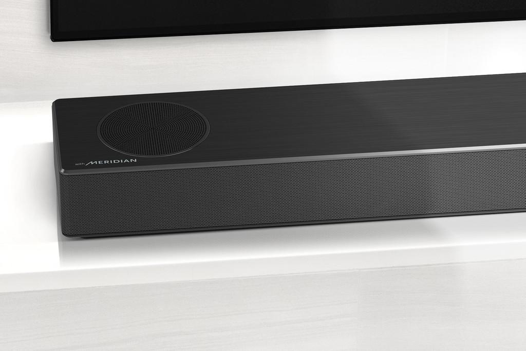 Prim-plan cu partea din stânga a soundbar LG, cu logo-ul Meridian afișat în colțul din stânga jos. Partea din stânga jos a televizorului este, de asemenea, vizibilă.