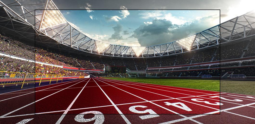 Ecranul TV prezintă un stadion, cu o pistă de alergare în prim-plan. Stadionul este plin cu spectatori.
