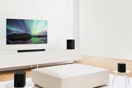 TV-ul și soundbar-ul într-o sufragerie cu design alb, având o canapea albă în centru. Difuzoarele sunt amplasate de o parte și de alta a canapelei.