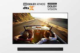 TV-ul și soundbar-ul în imagine completă. Pe televizor se afișează un cuplu într-o mașină decapotabilă care conduc la căderea serii.
