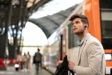 Imagine de stil de viaţă cu un bărbat așteptând în stație și purtând căştile WF-1000XM3