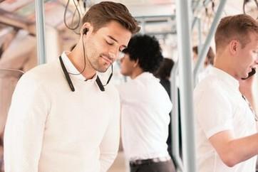 Imagine de stil de viață cu un bărbat bucurându-se de căștile WI-1000XM2 într-un mijloc de transport în comun.