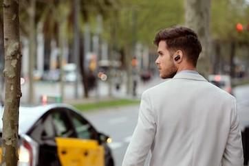 Imagine de stil de viaţă cu un bărbat mergând în timp ce poartă căştile WF-1000XM3