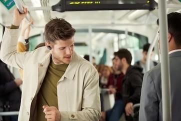 Imagine de stil de viaţă cu un bărbat bucurându-se de căştile WF-1000XM3 într-un mijloc de transport în comun.