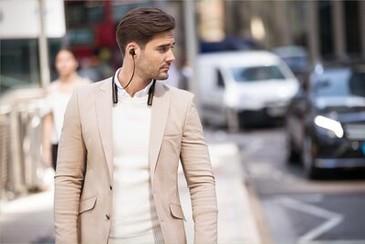 Imagine de stil de viață cu un bărbat mergând în timp ce poartă căștile WI-1000XM2