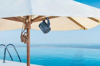 Imagine cu boxa wireless portabilă XB13 EXTRA BASS(TM) atașată de un parasolar pe o plajă tropicală.