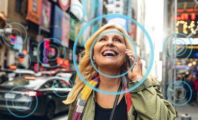 Femeie pe o stradă aglomerată, demonstrând modul în care Voice Zoom 2 îmbunătățește calitatea vocilor