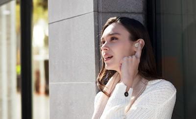 Imagine de stil de viaţă cu o femeie folosind asistentul vocal cu căştile WF-1000XM3.