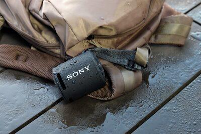 Imagine cu o boxă wireless portabilă sub jet de apă, ilustrând rezistența la apă.