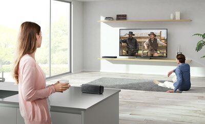 Cuplu uitându-se la televizorul, unul în plan apropiat, celălalt în plan îndepărtat