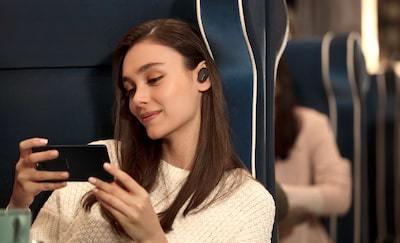 Imagine de stil de viaţă cu o femeie folosind căștile WF-1000XM3 pentru a se bucura de conţinut video pe smartphone.