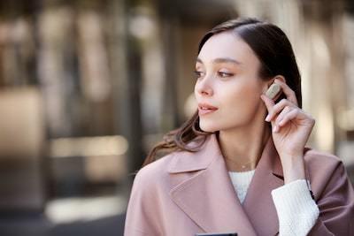 Imagine de stil de viaţă cu o femeie punând la loc în ureche o cască WF-1000XM3.