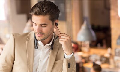 Imagine de stil de viață cu un bărbat folosind controalele pe fir de pe căștile WI-1000XM2.