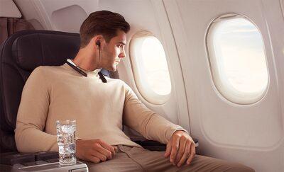 Imagine de stil de viață cu un bărbat ascultând la căștile WI-1000XM2 într-un avion