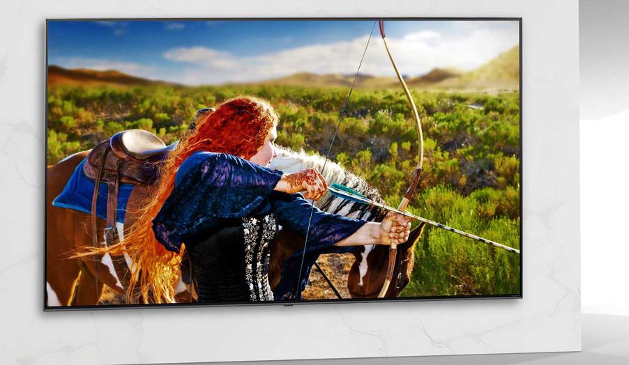 Ecran TV care prezintă o scenă dintr-un film SF, cu o femeie care trage cu arcul