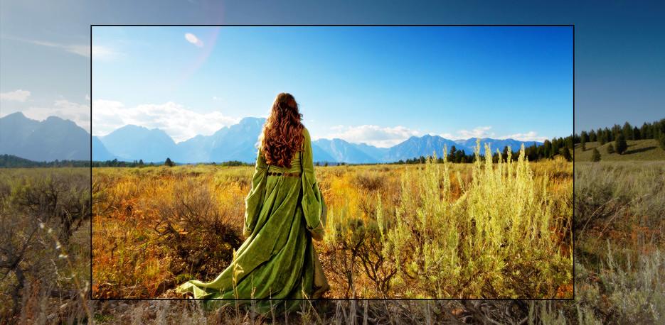 Un ecran TV care prezintă o scenă dintr-un film fantastic, cu o femeie care stă pe o câmpie, cu fața spre munți.