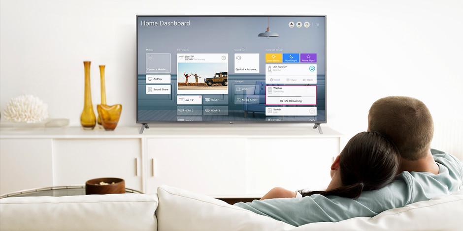 Un bărbat și o femeie care stau pe o canapea în camera de zi, cu Home Dashboard pe ecranul TV.